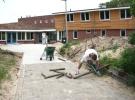 22 Juni: De Poolse helper van de Internationale Jeugd is bezig met het maken van een mooie rand voor het toegangspad